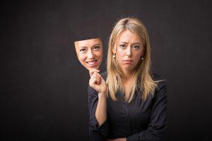 woman removing mask of limiting karma